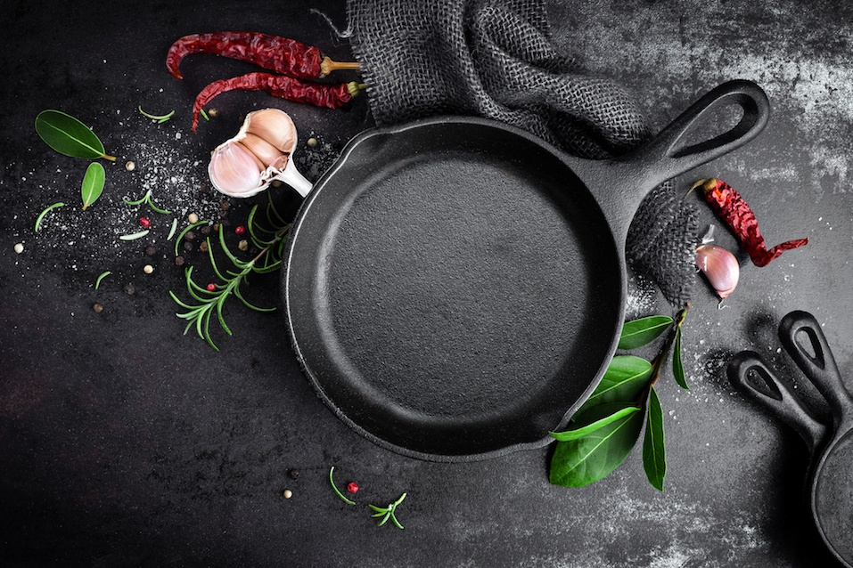 cast-iron-pan-and-spices-on-black-metal-culinary-background