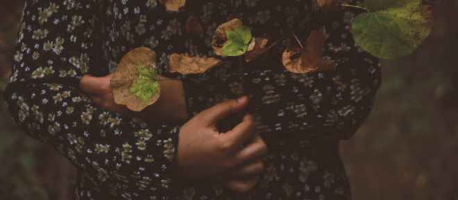 photo of person wearing black and white floral long sleeved shirt with leaves all over in top